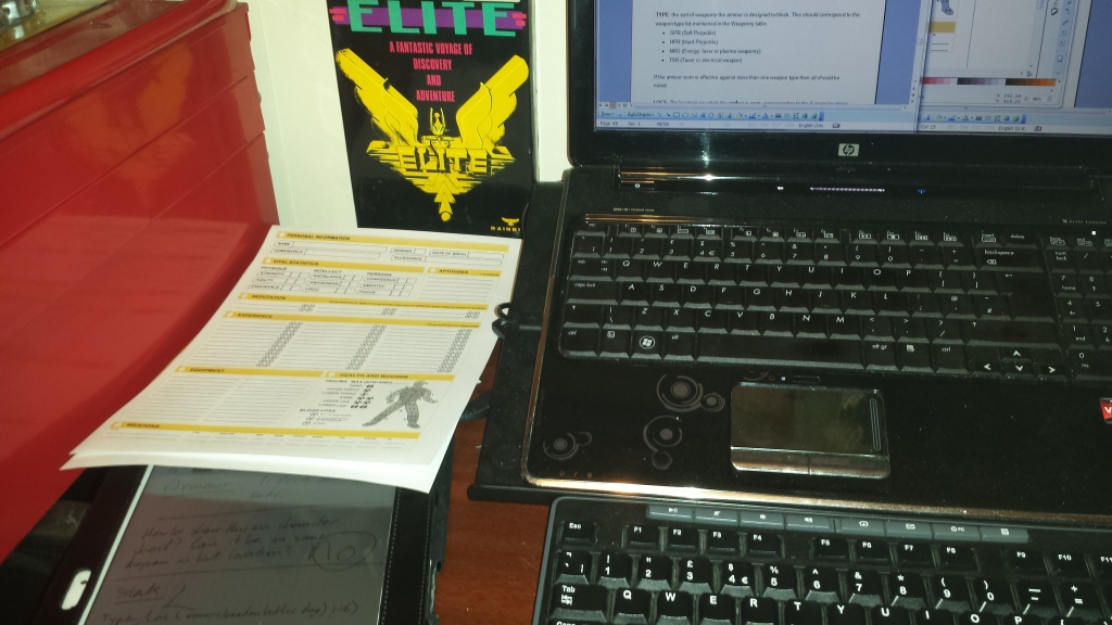 A laptop on the right hand side showing some graphics being designed. To the left is a copy of the original Elite and character sheets for Elite Encounters.